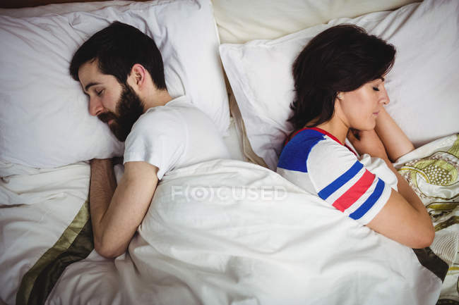 Couple sleeping together on bed at bedroom — Stock Photo