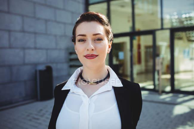Ritratto di giovane imprenditrice sorridente contro la costruzione — Foto stock