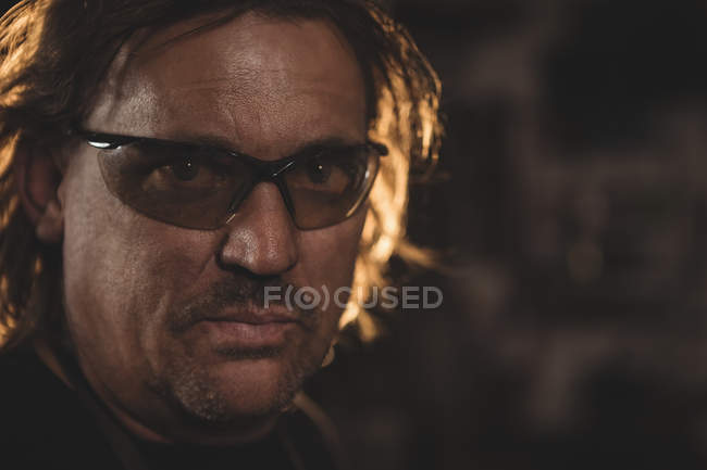 Портрет кузнеца в защитных очках в мастерской — стоковое фото