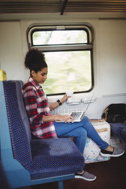 Full length of young woman using laptop while sitting in train — Stock Photo