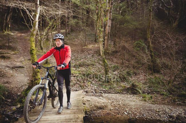 Горный велосипедист гуляет на велосипеде по пешеходному мосту в лесу — стоковое фото