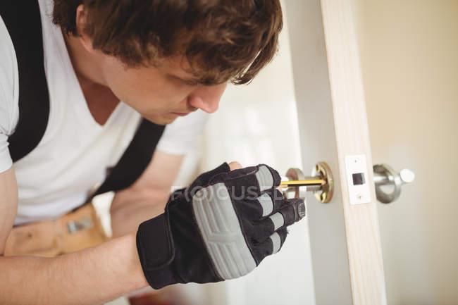 Carpintero fijación cerradura de la puerta en casa - foto de stock