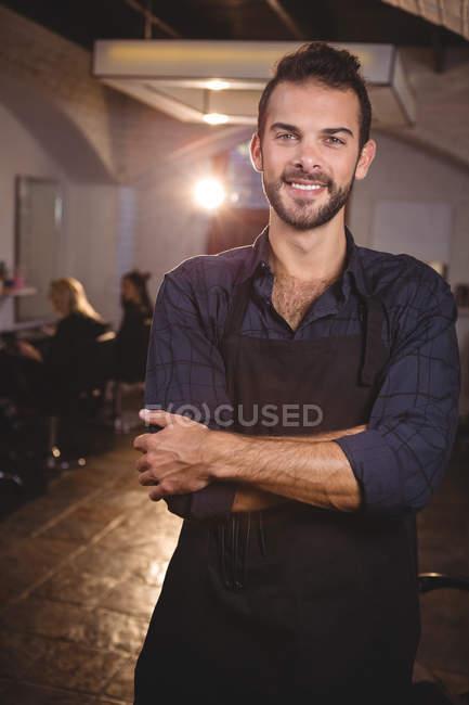 Портрет чоловічого перукар, стоячи з руки перетнув в салоні — стокове фото