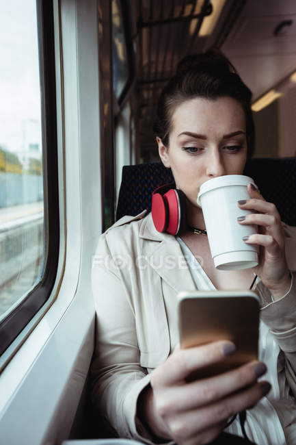 Young woman using mobile phone while drinking coffee in train — Stock Photo