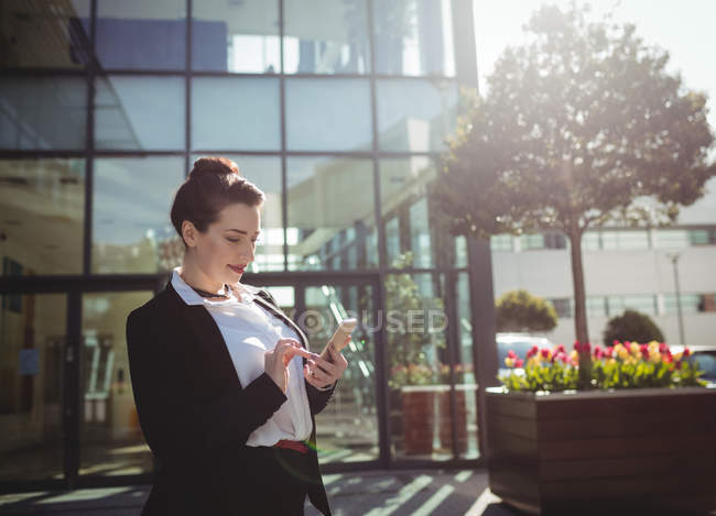 Young woman using mobile phone outside office building — Stock Photo
