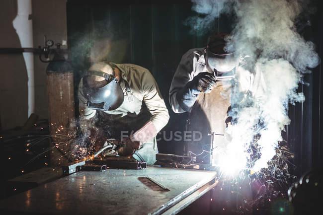 Зварювальники зварювання металу в майстерні — стокове фото