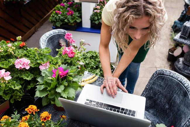 Жіночий флорист, використовуючи ноутбук у Садовому центрі — стокове фото