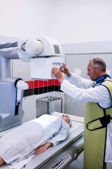 Médico usando máquina de rayos X para examinar al paciente en el hospital - foto de stock