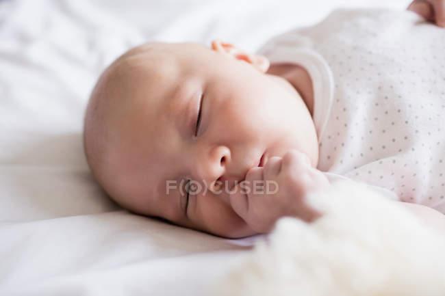 Прелестный ребенок спал на кровати с мишкой дома — стоковое фото