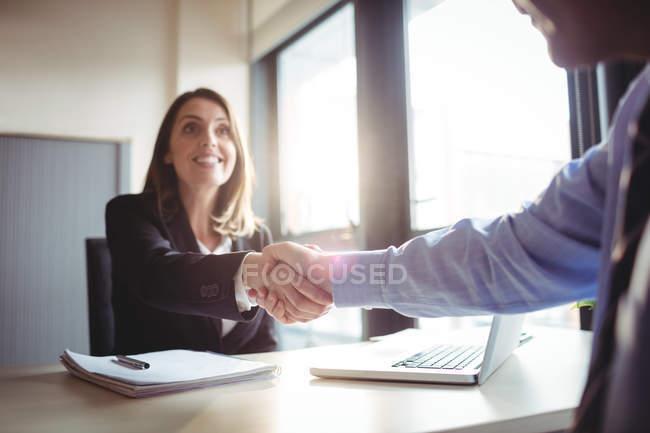 Обрезанный образ предпринимательницы, пожимающей руку коллеге в офисе — стоковое фото