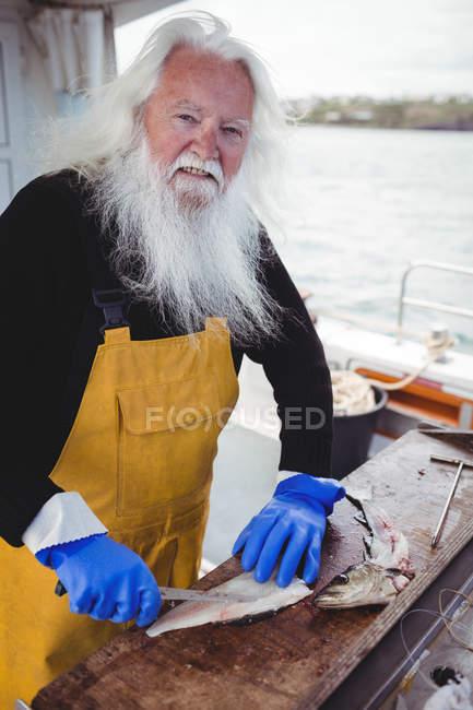 Porträt eines Fischers beim Filetieren von Fischen im Boot — Stockfoto