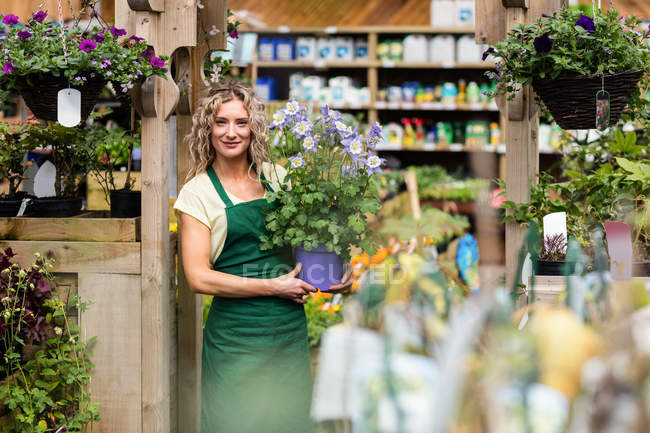 Portrait of female florist holding potted plant in garden centre — Stock Photo