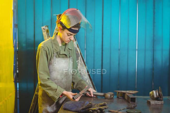Female welder examining piece of metal in workshop — Stock Photo