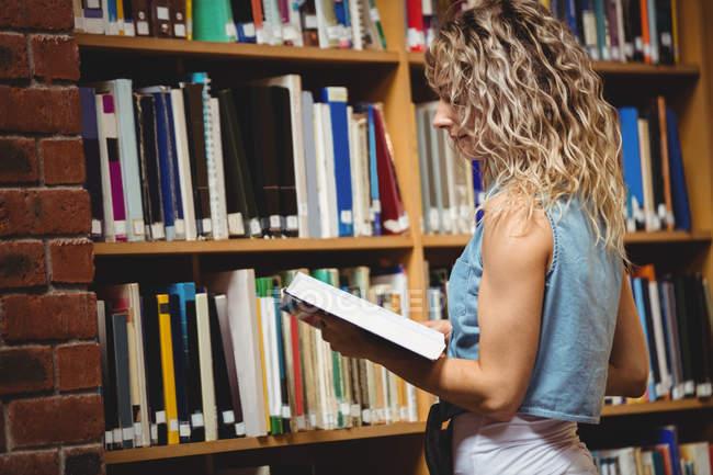 Livre de lecture de belle femme en bibliothèque — Photo de stock