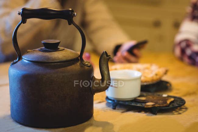 Teapot and cup on a table at home with people in background — Stock Photo