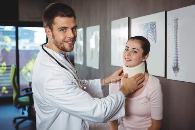 Retrato de fisioterapeuta examinando pescoço de paciente feminino na clínica — Fotografia de Stock
