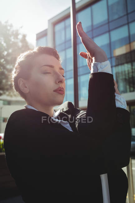 Thoughtful businesswoman with eyes closed stretching hands — Stock Photo