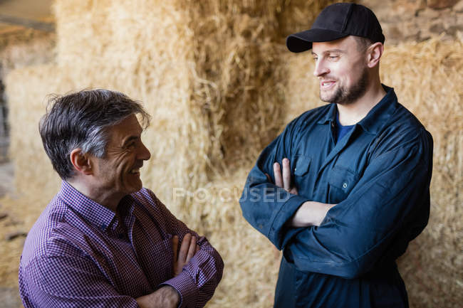 Happy farmer and vet talking while standing against hay bales at barn — Stock Photo