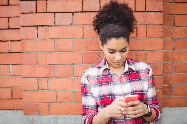 Giovane donna utilizzando il telefono cellulare mentre appoggiato sul muro di mattoni — Foto stock