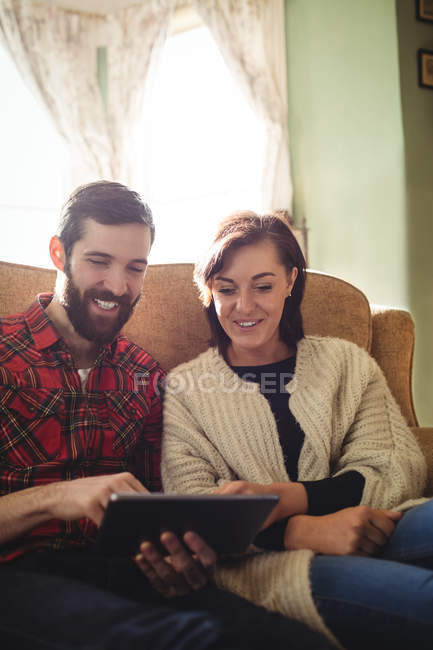 Coppia utilizzando tablet digitale in soggiorno a casa — Foto stock