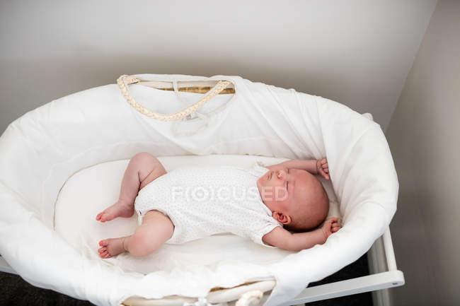 Bebé recién nacido durmiendo en la cesta de Moisés en casa - foto de stock