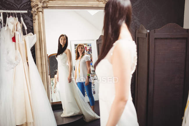 Mulher tentando no vestido de noiva em estúdio com a ajuda do designer criativo — Fotografia de Stock