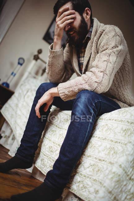 Депрессии человек, сидя на кровати в спальне — стоковое фото