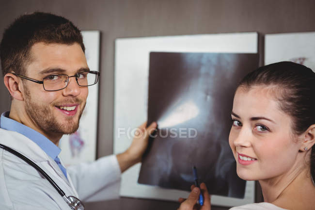 Portrait of physiotherapist explaining spine x-ray to female patient in clinic — Stock Photo