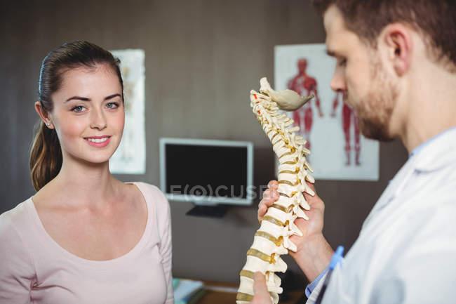 Fisioterapista con modello di colonna vertebrale mentre il paziente sorride alla telecamera in clinica — Foto stock