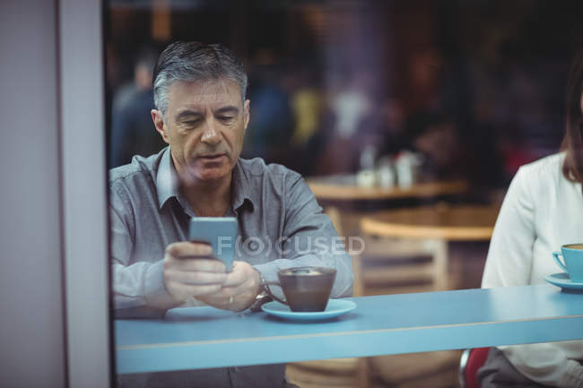 Uomo che utilizza telefono mobile nella caffetteria — Foto stock