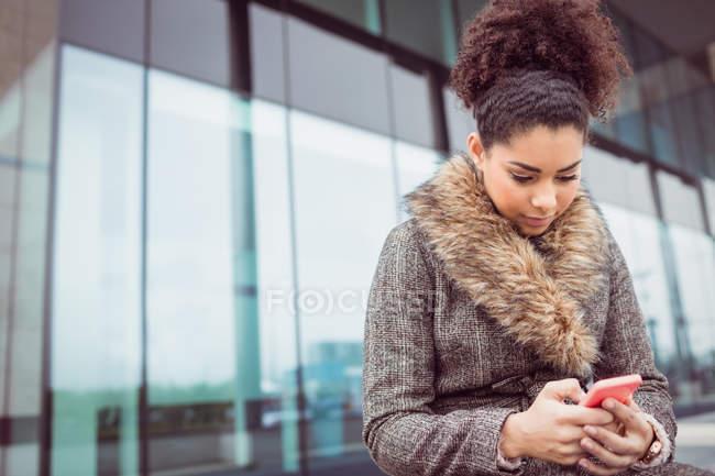 Низкий угол обзора молодой женщины, использующей телефон против здания — стоковое фото