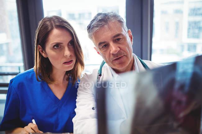 Doctor and nurse examining x-ray at hospital — Stock Photo