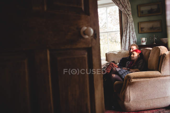 Romantic hipster couple relaxing on sofa seen from doorway at home — Stock Photo