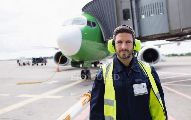 Portrait of airport ground crew standing on runway at airport terminal — Stock Photo