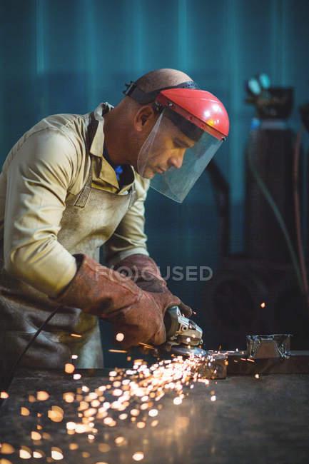 Male welder working on piece of metal in workshop — Stock Photo