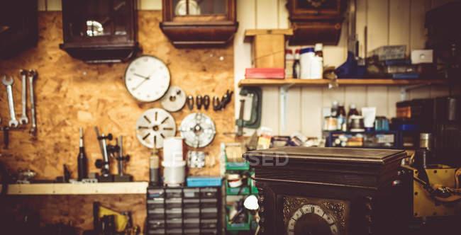 Alte Uhrmacher-Werkstatt mit Reparatur von Werkzeugen, Ausrüstungen und Uhren an der Wand Uhr — Stockfoto