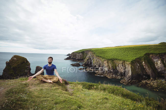 Man performing yoga on cliff — Stock Photo