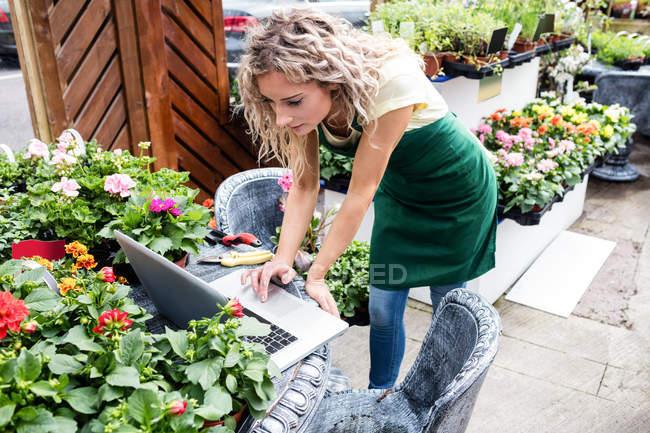 Женский флорист с ноутбуком в центре сада — стоковое фото