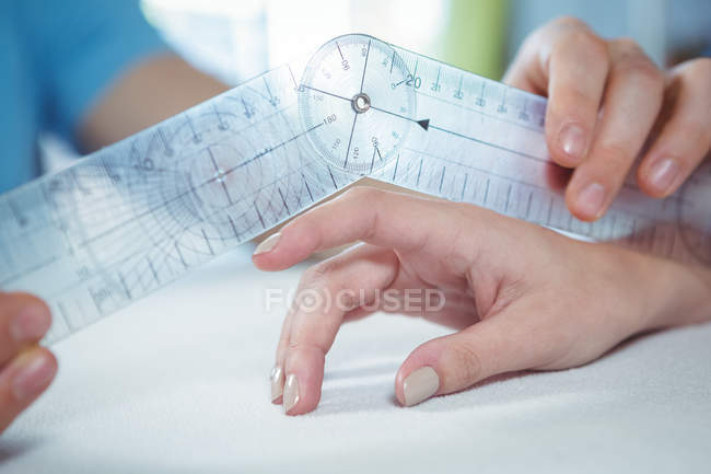 Cropped image of physiotherapist examining female patient finger with goniometer in clinic — Stock Photo