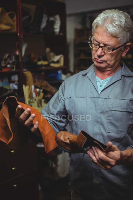 Mature shoemaker examining a boot and piece of material in workshop — Stock Photo