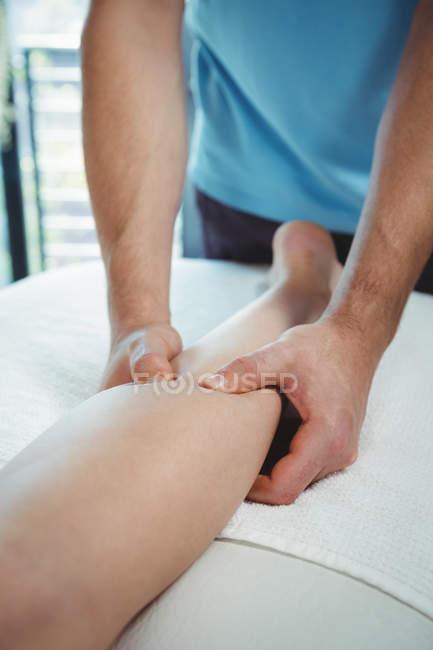 Imagen recortada de fisioterapeuta que da fisioterapia a la pierna de la paciente femenina en la clínica - foto de stock