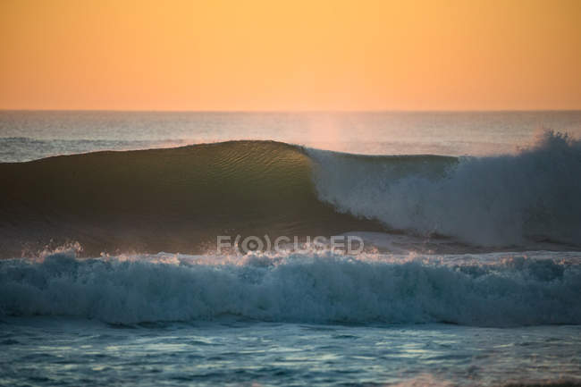 Waves crashing at sunset at the beach — Stock Photo