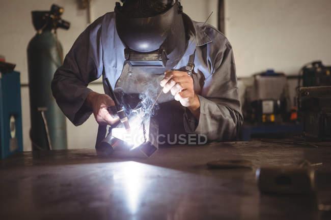Сварщик сварочный металл в мастерской — стоковое фото