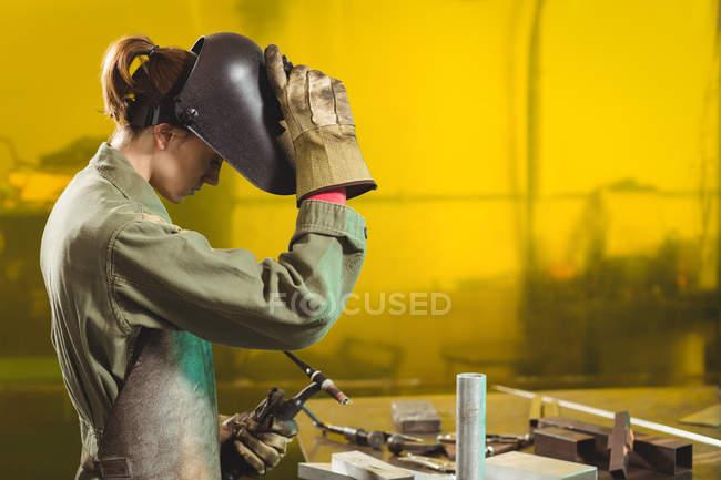 Жіночий зварювальник, тримаючи факел зварювання в майстерні — стокове фото