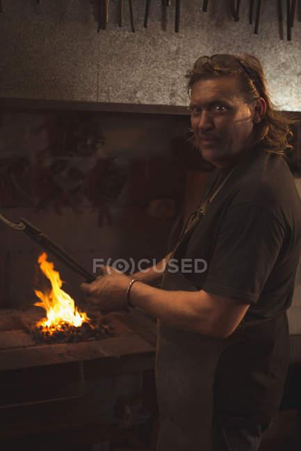 Forgeron chauffant un morceau de métal dans l'atelier — Photo de stock