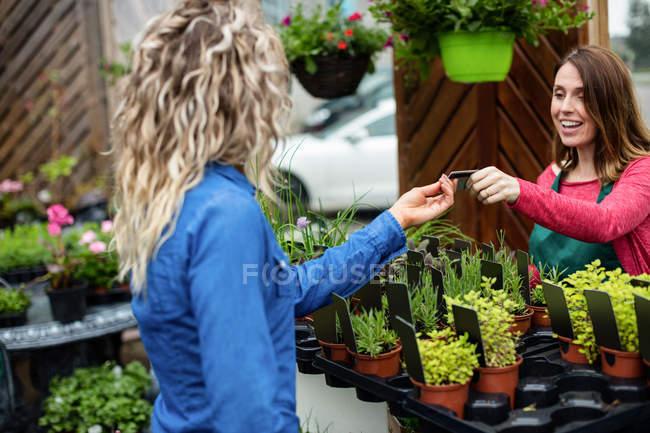 Жінка внесення оплати кредитною карткою її до флорист в садовому центрі — стокове фото