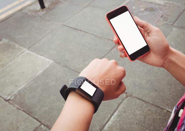 Bild der Frau trägt Armbanduhr Handy mit gedrückter beschnitten — Stockfoto