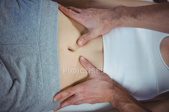 Обітнутого зображення чоловічого фізіотерапевт, даючи шлунка масаж пацієнтки — стокове фото