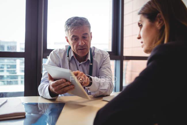Arzt, diskutieren mit Patienten über digital-Tablette im Krankenhaus — Stockfoto