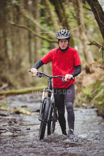 Portrait of biker walking with bicycle in stream at forest — Stock Photo